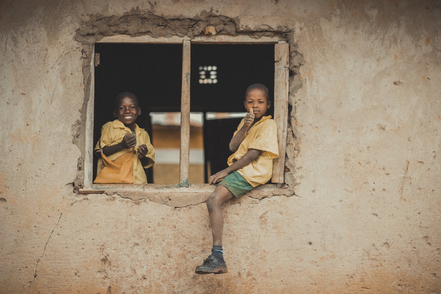 boys in school uniform sitting on window frame of an unfinished classroom