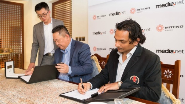 Divyank Turakhia (R) and Zhang Zhiyong (C) sign the acquisition agreement